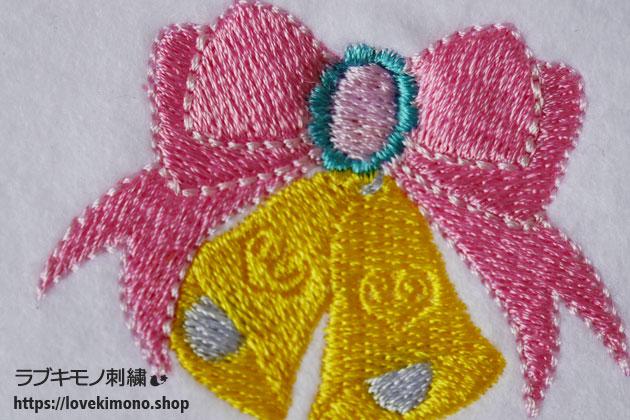 黄色のベルとピンクのリボンの刺繍