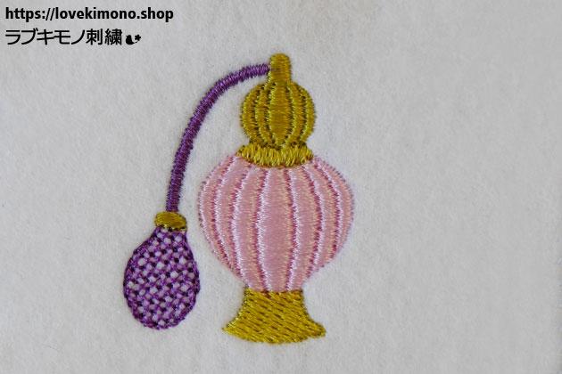 ピンク色の香水瓶、紫色のポンプの刺繍