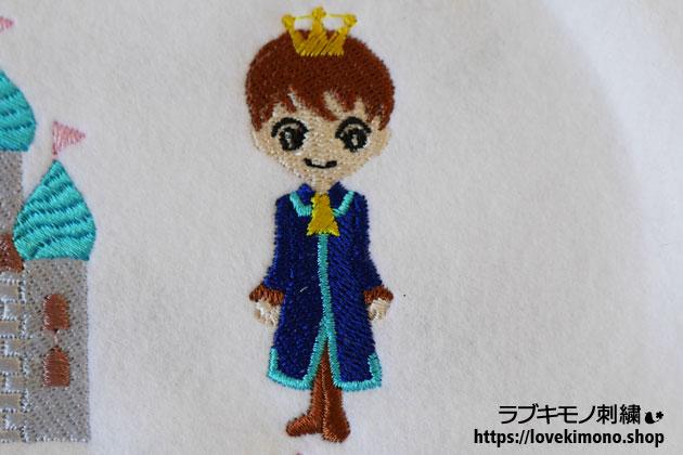 茶色のブーツ、青い服、黄色の王冠の王子様の刺繍
