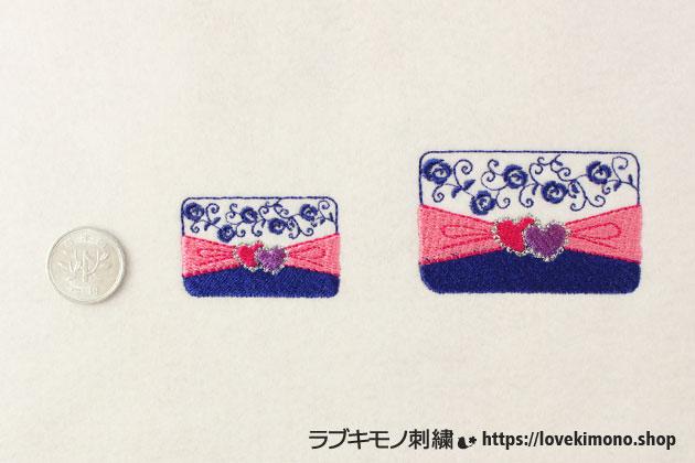 かわいいハートマーク、ほうせき、ばらのクラッチバックの刺繍、大小サイズを1円玉と比べる