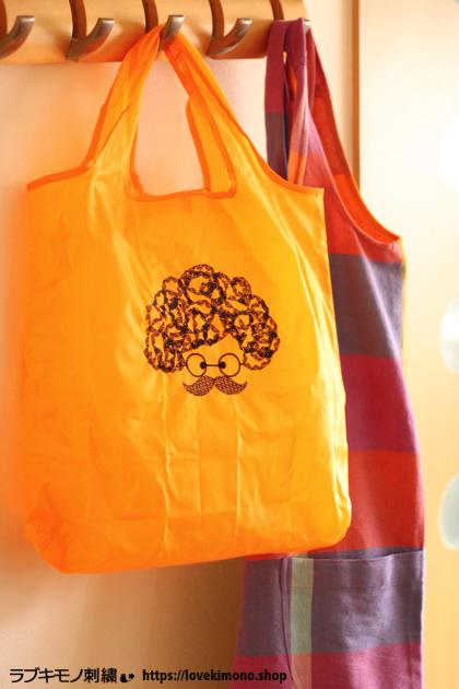 オレンジ色のエコバックにもじゃもじゃ頭の刺繍