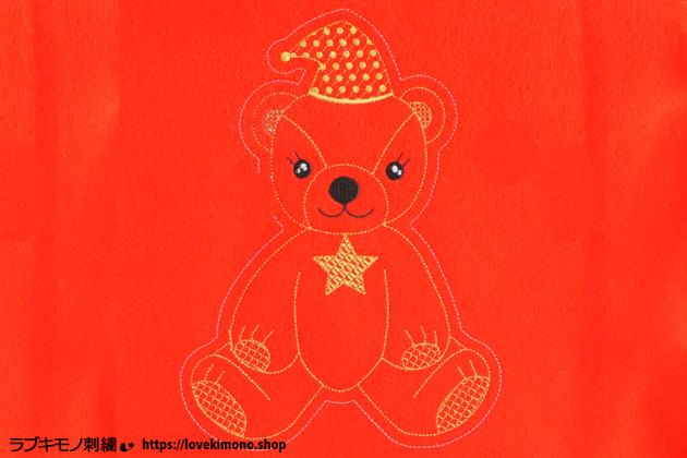 赤いフェルト生地に刺繍した、かわいいクマのぬいぐるみ
